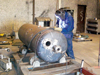 A worker putting the finishing touches to a tank at an Inco fabrication shop